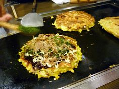 "Okadaman food truck in NYC. ""Fill up on okonomiyaki, a pancake/omelet hybrid of chopped cabbage, seaweed, ginger, and pork doused in special batter (it involves yams and eggs). Chef Okada Yasuhiko grills the mix 'til crisp and serves with scallions, tempura flakes, and specialty mayo."""