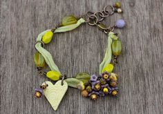 Wire wrapped beaded bracelet, czech glass flowers, Jasper rounds, brass chain, ceramic heart charm, green yellow tones lilac. £18.00, via Etsy.