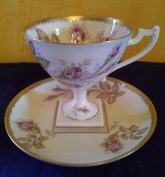 Limoges France porcelain tea cup, saucer with matching dessert plate in a lovely rosebud pattern. All of the pieces are bordered in gold. The tea cup has an unusual square base which fits the matching