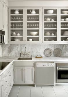 Pretty Warm Gray Cabinets with Carrara Marble Countertops and Slab Backsplash