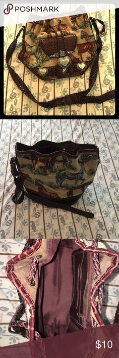 Western purse Dark brown leather, silver buckles, braided strap. Pull leather straps to close. Horses detailed on bag; leather bottom. Dark brown inside with 2 small pockets. Back pack style but over the shoulder. Bags Crossbody Bags