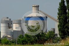 Photo made in Monselice in the province of Padua (Italy). The picture shows the large cement factory which is located in the north and near the town. Although it is a structure of industrial production aesthetics it can be considered interesting. A portion of the structure is located behind the two tall poplar trees to the right of the image.