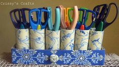 Use toilet paper rolls glued to a shoe box lid to hold various scissors!
