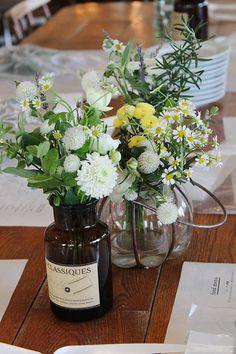 CAFE HAUSさんので会場装花。ゲストテーブルにはブラウンのメディシンボトルやアンティーク風の花瓶に野の花をざっくりといけてナチュラルな雰囲気に。 wedding,reception, party,decor, natural, green,garden,centerpiece,medicine bottle,,glass,antique