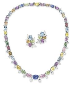 A SET OF MULTI-COLORED SAPPHIRE AND DIAMOND JEWELRY. Comprising a necklace, designed as a graduated series of oval-cut multi-colored sapphires, spaced by baguette, circular and heart-shaped diamond links; and a pair of ear clips en suite, mounted in platinum.
