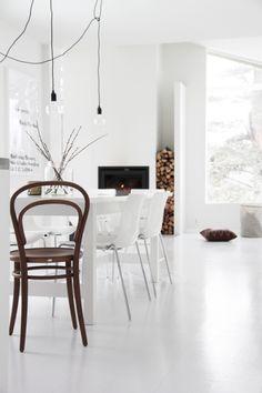 żarówki na kablu w białym salonie z kominkiem w minimalistycznym stylu