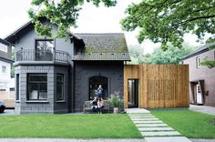 A family of cost-conscious Hamburgers converted a kitschy turn-of-the-century villa into a high-design home with a strict budget in place. To unite the quaint masonry of the original villa with the squat, ugly add-on built flush against it, the architects decided to paint the old-fashioned facade graphite gray and then covered the box next door in plain, light-colored larch.  Photo by: Mark Seelen