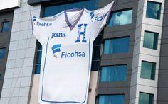 Una bandera que representa la camiseta oficial de la Selección de fútbol de Honduras se cuelga de un edificio en Tegucigalpa, Honduras, a sólo dos semanas antes del inicio del torneo de fútbol de la Copa Mundial de Brasil 2014. Foto: Orlando SIERRA #Brasil2014 #Fifaworldcup2014