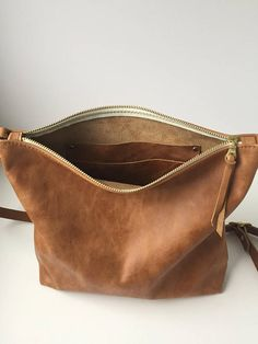 Leather Crossbody Bag in a beautiful distressed saddle brown leather. Your new go-to bag - with an updated design! This is the perfect bag to stash all of your essentials. Roomy enough to fit your wallet, phone, keys, sunscreen, etc, but with a convenient (and removable!) and now