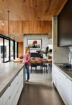 A concrete kitchen benchtop complements the concrete flooring of this coastal home. Timber panelling on the ceiling adds wramth.