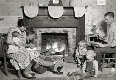 November 1933. Family group of Fletcher Carden, Route 1, Andersonville, Tennessee. A night-watchman at the Norris Dam bunkhouses. His home is on the townsite of Norris and will be moved. Carden has 12 children. He is shown here repairing shoes at the fireside.