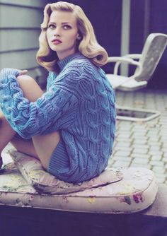Retro hair and makeup and a chunky knit sweater.