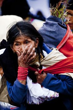 Old woman at Otavalo market carrying a load on her back, Otavalo, Ecuador