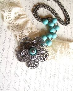 The focal point of this handmade necklace is the beautiful filigree flower pendant in antique silver finish followed by a strand of turquoise pearl beads and a vintage chain in antique silver finish as well.
