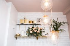 "In the little dining nook, the ""Cloud Pendant Chandelier"" is from Arteriors, the black and white geo marble shelf is from Anthropologie, and the gold wine shelf is from Ballard Designs. Living Room Sofa, Apartment Living, Living Room Decor, Apartment Therapy, Apartment Ideas, California Bedroom, Gold Shelves, New York Apartments, Manhattan Apartment"