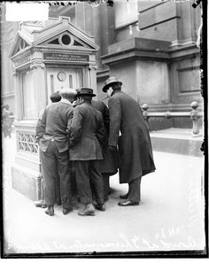 """Men standing in front of a """"weather kiosk"""", c.1914. This particular one was in front of the Federal Building on Adams. Look closely and you'll see a barometer and a thermometer on the front of the kiosk. This was probably one of the only places someone could find out the current temperature or read pressure values to predict pending weather."""