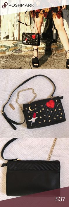 """PRICE FIRM💄NWT Lipstick & Heart Crossbody Bag PRICE FIRM UNLESS BUNDLED.💄 New with tags, crossbody bag with lipstick and heart appliqués. Also has pearl and star studs. Quilted faux leather black background. Zipper and magnetic closure. Goldtone and faux leather strap. 2 pockets inside. Lined in black fabric. Original price is $39.99. 9"""" wide, 6"""" long, 2"""" deep. Handle drop is 23"""" at longest length- is adjustable. Francesca's Collections Bags Crossbody Bags"""