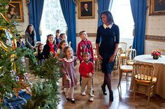 On Nov. 30, 2011, the First Lady opted for a simple black-and-white shift for a cookie-decorating event with military families in the White House's State Dining Room. It was also the first time people got a glimpse of the White House holiday decorations.