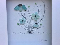 Pebble Art Genuine Sea Glass and Pebble Flowers in Shadow Box with Matting Modern Wall Art Abstract Contemporary Signed. This signed original pebble art is made by me, Susi Uhl. The pebble art is a unique style made of pebbles and genuine Sea glass collected by me and would be a perfect gift for any occasion. The art comes in a 16 x 12 shadow box frame with matting and glass. The inside dimensions of the matting are 8 x 10. The overall frame dimensions are 17 x 13 x 2 All my work is signed…