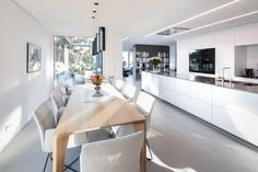 Die extrem lange Tischlerküche bietet sowohl genügend Platz, um aufwändige Gerichte zubereiten zu können, als auch eine gemütliche Sitzgelegenheit, welche zum Verweilen einlädt. Sie verfügt über glänzend aufpolierte Arbeitsplatten in einem warmen Braun-Grau, welches das Schwarz der Miele-Geräte und das Weiß der Verkleidungen ideal ergänzt. | Bilder: www.hassler.at | #küche #weiß #schlicht #elegant #nobel #minimalistisch #miele #dekton #lumina #küchen #tischler #tischlerei #vorarlberg…