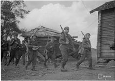 Finnish soldiers march as one plays the balalaika, August 1941.