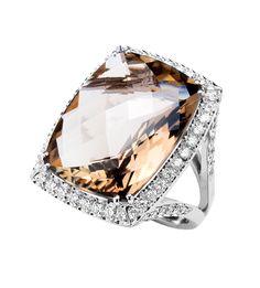 La sortija JUBA es una preciosa pieza de Oro blanco de Primera Ley en la que se combina los más selectos diamantes con el cuarzo fumee como pieza principal de la joya, creando un resultado sorprendente que quedará prendada a más de una en el momento de la pedida de la mano.