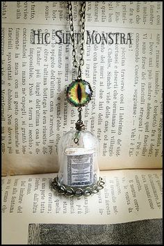 """""""Book Protector"""" - long necklace with glass globe protecting a miniature book inside, and a watcher in the form of a feline eye."""