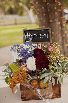 Love this chalkboard table number sign in a rustic floral arrangement