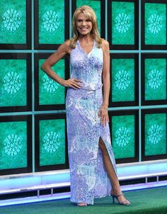 CACHE: Long jersey dress in royal blue, teal & turquoise abstract paisley print on white background, v-neck halter bodice, sleeveless, gold chain & fabric braided belt, straight skirt | Vanna White's dresses | Wheel of Fortune