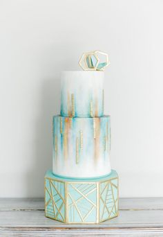 The watercolor turquoise, blue and teal wedding cake with gold geometric patterning was hand painted onto fondant by Style Me Sweet. Click for more Teal and Gold Wedding Ideas: http://www.confettidaydreams.com/teal-and-gold-wedding-ideas/