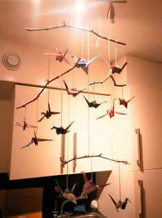 A classy rustic chime. Origami cranes made from old pamphlets tied on twigs