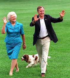 President George H.W. Bush and Barbara Bush walk with Millie across the South Lawn.