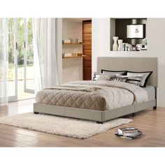 The Portfolio Holly upholstered queen sized bed is covered in a woven textured grey-green fabric and accented with one row of stitching down the center for a clean look. The queen bed includes a headboard, footboard, side rails and four wooden slats.