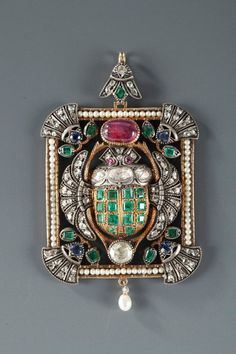 Striking silver and 14k gold-mounted pendant featuring a winged scarab beetle. The body of the beetle is decorated with square-cut emeralds, and a large, ruby cabochon. Designer unknown(639×960)