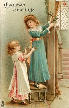 CHRISTMAS GREETINGS girl white /pink dress hands holly to girl in blue dress who is hanging it
