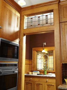 Craftsman-style leaded-glass transoms over an open archway door accent this vintage-look kitchen makeover