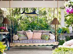 Gorgeous porch swing with printed pillows from Africa and India.  Palm Beach home of Liza Pulitzer Calhoun daughter of the late fashion designer Lilly Pulitzer