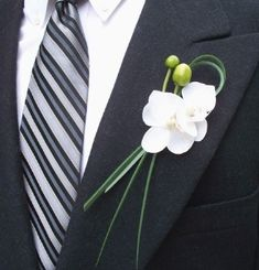 This boutonniere consists of 2 white phalaenopsis orchid blooms with bear grass.