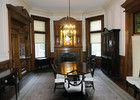 The formal dining room at Elmwood Mansion includes an unusual fireplace with a stained-glass window. The chimney flu goes up on either side of the window. Kentucky