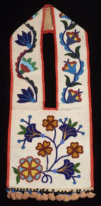 Ojibwe : This bag, which has no pocket, is fully beaded with a floral pattern against a white background. Trimmed with thick red polyester fabric, the bag has large black and blue bead dangles with salmon colored yarn tassels. It is lined with cotton calico.