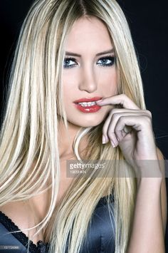 Beautiful blond woman in dark elegant clothes,studio shot.