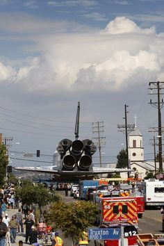 The space shuttle Endeavour approaches the intersection of La Tijera Boulevard and Manchester Avenue as it is transported to the California Science Center in Exposition Park from Los Angeles International Airport (LAX) on October 12, 2012 in Los Angeles, California. Endeavour was flown cross-country atop NASA's Shuttle Carrier Aircraft from Kennedy Space Center in Florida to LAX on its last flight ever on September 21. From there, it was transported to the California Science Center in ...