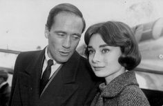 """The actress Audrey Hepburn photographed with her husband Mel Ferrer (actor, dialogue coach and film director) during their arrival at the London Airport (known as """"Heathrow Airport"""" since 1965) in London (England), on November 16, 1956. Audrey was..."""