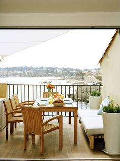 Contemporary Mediterranean Patio Table and chairs on a balcony overlooking a harbor.