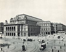 An imposing, heavily ornamented building in a city location, with numerous horsedrawn vehicles and pedestrians passing. There are visible tramlines in the street./Jewish orchestra
