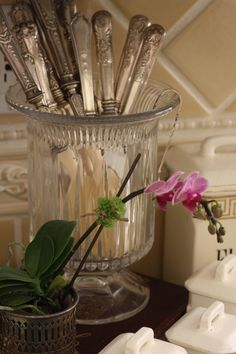 Use flower vases to hold silver on a buffet table.