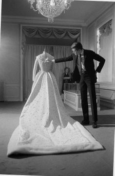 December 1959 Yves examines the wedding dress he designed of Dibah Farah, Empress of Iran.