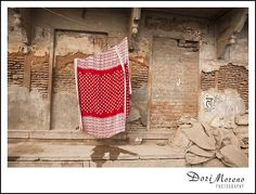 A bright red tablecloth stands out against the drab broken brick wall, India Red Tablecloth, Incredible India, Amazing, Brick Wall, Dory, Color Splash, The Incredibles, Frame, Prints