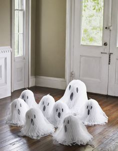 DIY Gang of Ghosts by Kristi Cameron, Countryliving: Make these cuties with black paper eyes glued onto white tissue-paper bells and draped with cheesecloth.