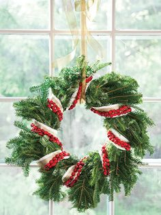Spruce up an evergreen wreath with white ribbon, spacing each round 4 to 6 inches apart. Wrap strung cranberries around the wreath, layering over the ribbon. (Photo: Jennifer Davick)